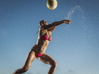 Water splashing on woman playing volleyball