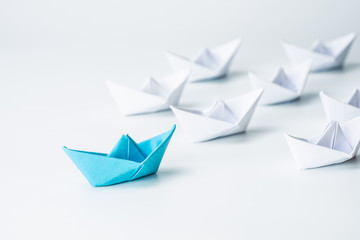 Leadership concept with blue paper ship leading among white on white background.