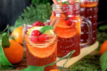 Punch with cranberries and orange decorated with mint and a stick of cinnamon in glass vessels