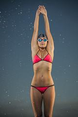 Water splashing on Caucasian woman preparing to dive into swimming pool