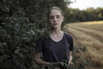 Portrait of Caucasian teenage girl holding branch