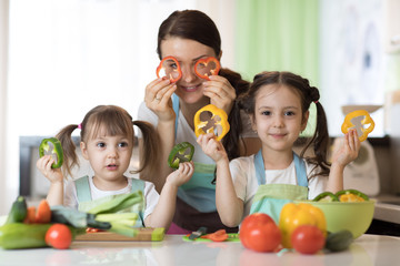 mother and children preparing healthy food and having fun