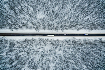 freight car drive along the road through the winter forest. Road seen from the air. Aerial view landscape. shooting from a drone