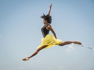 Water spraying on black woman ballet dancing