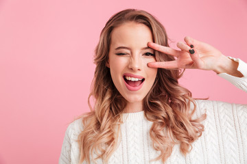 Cheerful young woman showing peace gesture.