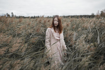 Stylish young woman standing in windy marsh grass