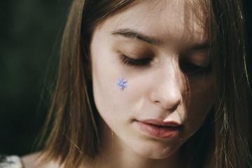 Caucasian woman with flower jewelry on cheek