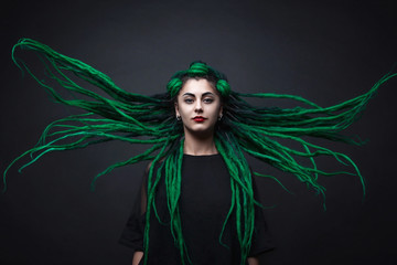 Pretty girl with green long dreadlocks. Black background.