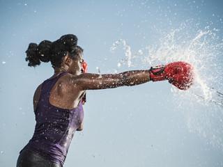 Water spraying on black woman boxing