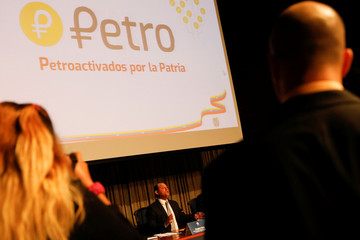 The new Venezuelan cryptocurrency the Petro logo is seen as Minister for University Education, Science and Technology Hugbel Roa talks to the media during a news conference in Caracas