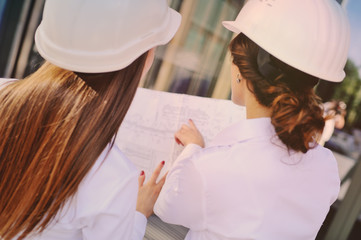 Two young pretty business women industrial engineers in construction helmets with a tablet in hands on a glass building background