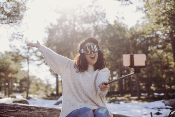 young beautiful woman sitting on wood trunks and taking a picture with mobile phone. Wearing ski goggles. Back light. Outdoors and lifestyle