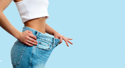 Weight loss. Woman in oversize jeans on pastel blue background