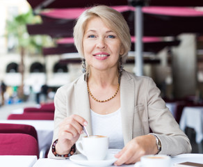 Portrait of elegant mature female who is enjoying of lunch with coffee