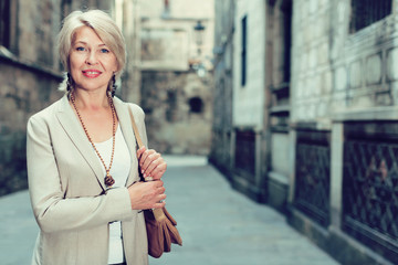 Elegant mature woman is posing in time walking