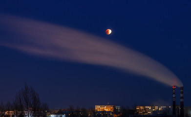 Lunar eclipse on January 31, 2018 against the background of a dark sky and smoke from a pipe. Eclipse, the super moon, the full moon. Western Siberia. The peak phase of the lunar eclipse.