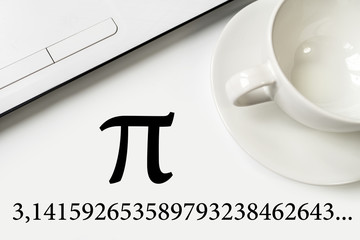 International Pi Day. On a white table a laptop and a cup.