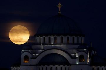 A full moon rises behind St. Sava temple in Belgrade