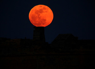 A full moon 'supermoon' rises behind Fort Ricasoli in Valletta's Grand Harbour