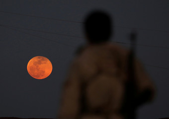 A fighter from Free Syrian Army is seen watching a full moon rises in Daraa