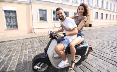 Cheerful young couple riding a scooter and having fun