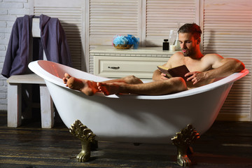 Sexuality and relaxation concept: man with beard reading book