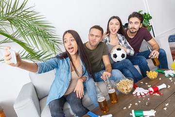 Group of friends sport fans watching soccer match taking pictures