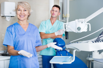 Dentist near dental chair, welcoming patient to office
