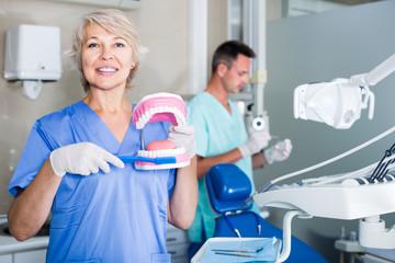 Smiling female stomatologist demonstrating tooth brushing on jaw model