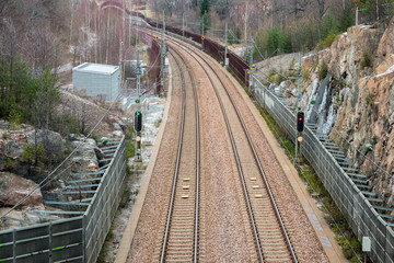 View from above of double railroad tracks in a mountain and forest evironment.