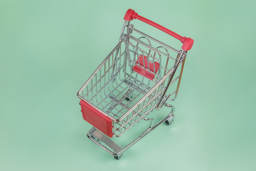 Closeup of tiny shopping cart on green background
