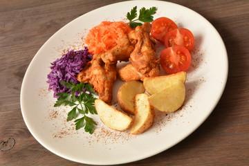 skrzydełka z kurczaka pieczone z ziemniakami, surówkami i pomidorem