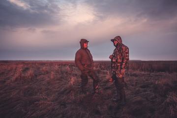 Hunters during hunting spring season in rural field at sunrise