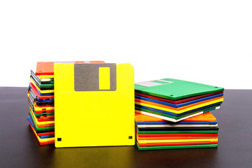 Horizontal shot of two stacks of old plastic disks with a yellow disk standing up against one stack.  Front side showing.  Dark table surface and white wall behind them.