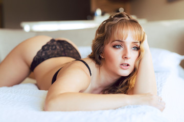 Attactive young Caucasian woman with big eyes and black underwear reclines on a bed
