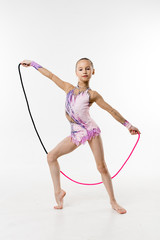 A young teenage girl shows gymnastic and ballet exercises on a white background.