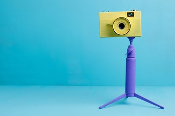 Bright retro vintage camera on tripod on blue background, copy space. Photography concept