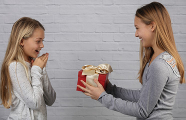 Portrait of happy teen age girl giving present to her younger sister. Family, childhood concept