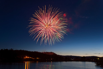 Celebration Fireworks Display Over a Mountain Lake at Dusk