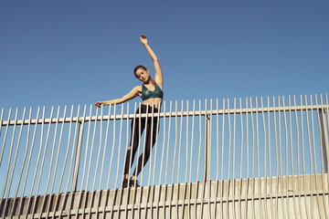 Low angle view of young woman exercising on bridge against clear sky