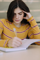 Woman writing on book while sitting at table in library