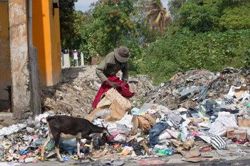 man digging thru the trash in third world country