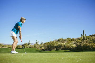 Side view of woman playing golf at a golf course