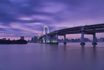 Rainbow bridge over river with Tokyo tower and sky during sunset