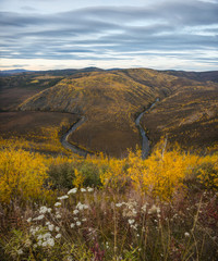 View of river amidst landscape against sky during autumn