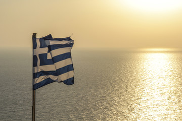 Greek Flag waving by sea against sky during sunset