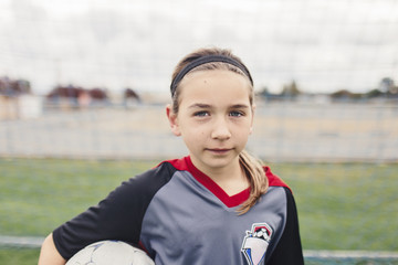 Portrait of confident girl holding soccer ball while standing on field