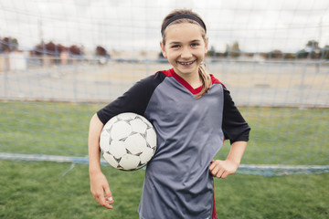 Portrait of smiling girl holding soccer ball while standing on field