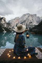 Rear view of woman holding lantern while sitting by lake against mountains