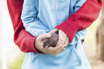 Midsection of mother holding son's hands at park